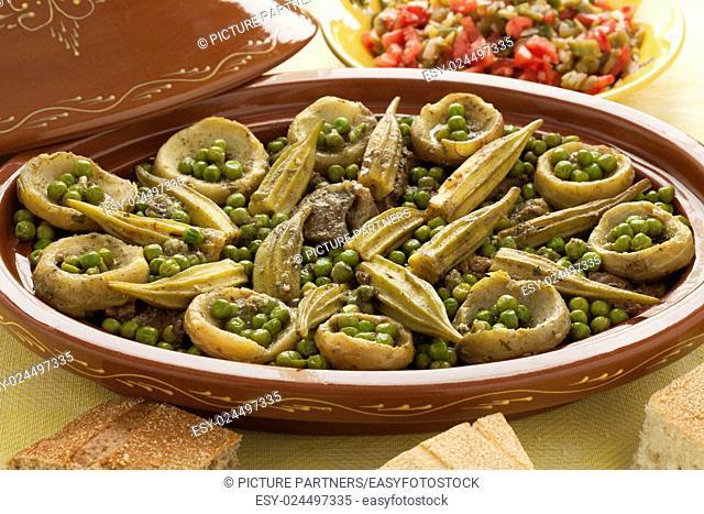Moroccan oval tajine with meat, okra, green peas and artichoke hearts