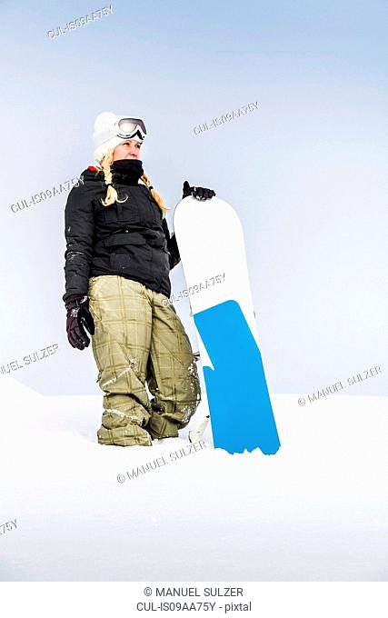 Portrait of young female with snowboard, Reutte, Tyrol, Austria