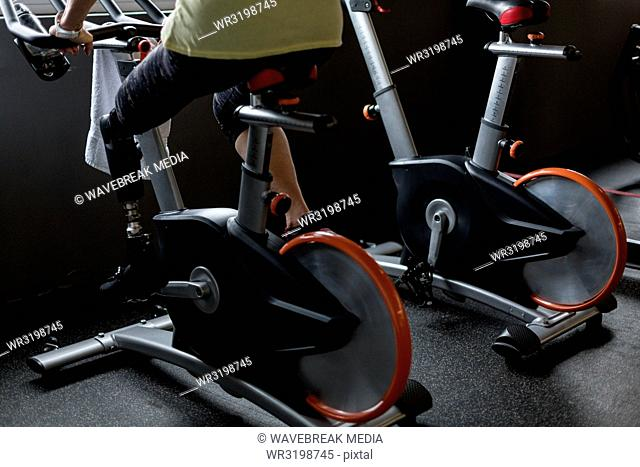 Woman exercising on a gym cycle