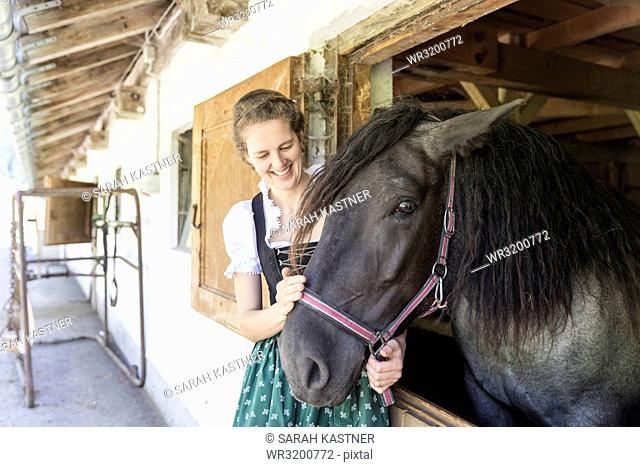 Countrywoman with dirndl petting a horse