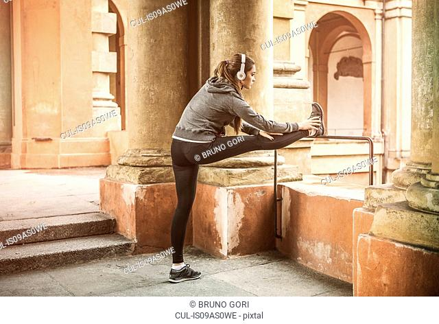 Young woman wearing sports clothes and headphones stretching legs