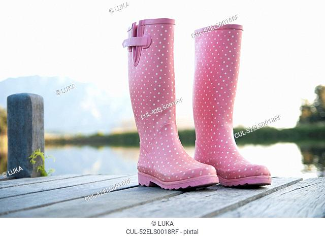 Pink rainboots on wooden dock
