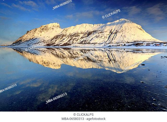 The snow capped mountains reflected in Steiropollen lake at sunrise, Lofoten Islands, Norway Europe
