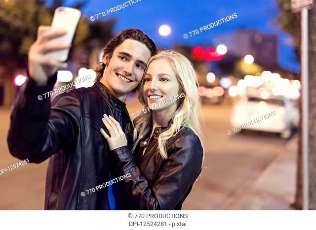 A young couple take a self-portrait with a smart phone along a street at dusk; Edmonton, Alberta, Canada