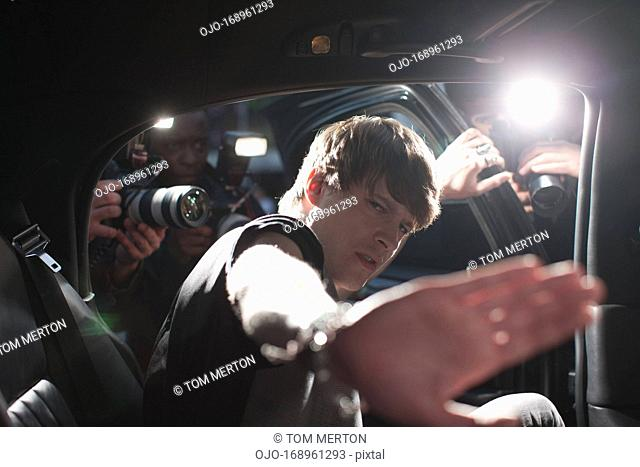 Celebrity blocking photo in backseat of limo
