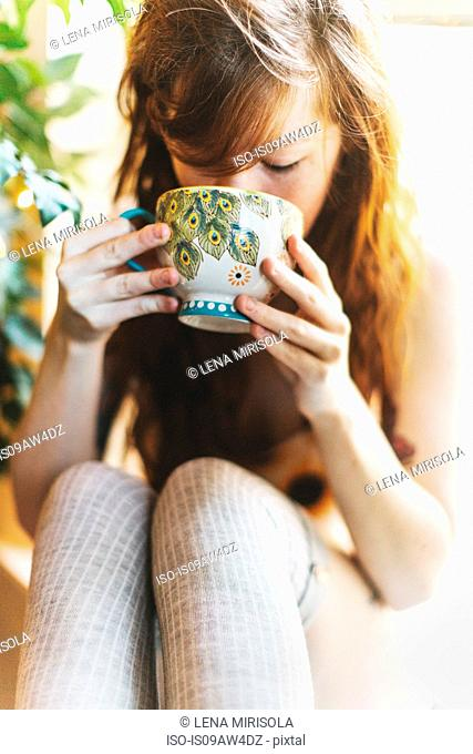 Young woman drinking from teacup