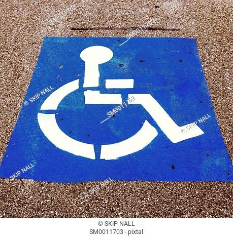 A sign painted in a parking lot indicating a parking place is for handicapped parking only
