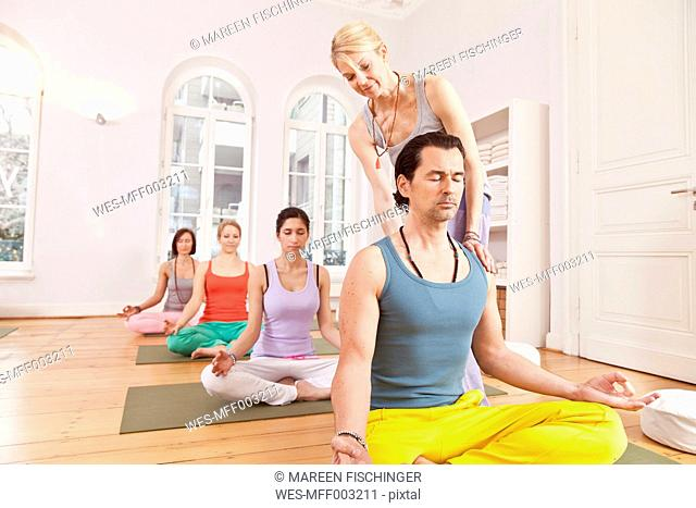Group of people in yoga studio sitting in Lotus pose while instructor straightens their backs
