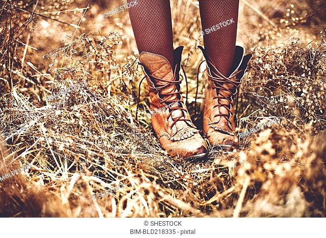 Boots of Caucasian teenage girl standing in tall grass