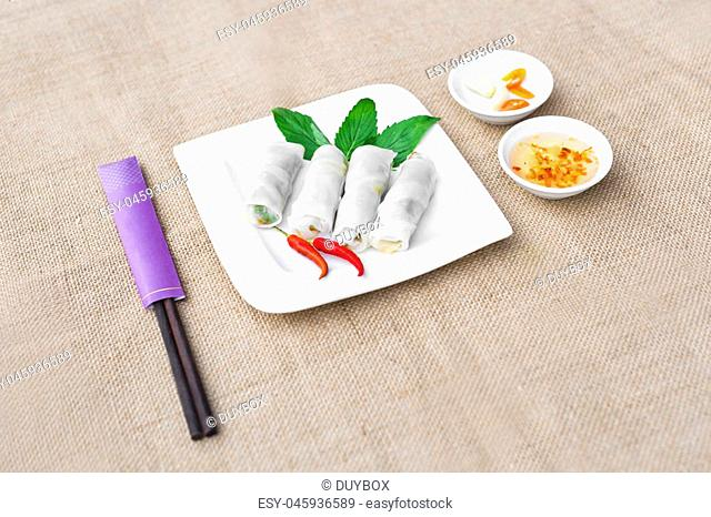 Vietnamese steamed thin rice pancake for fried pork rolls or banh uot Hue with lettuce, herbs and chili sauces
