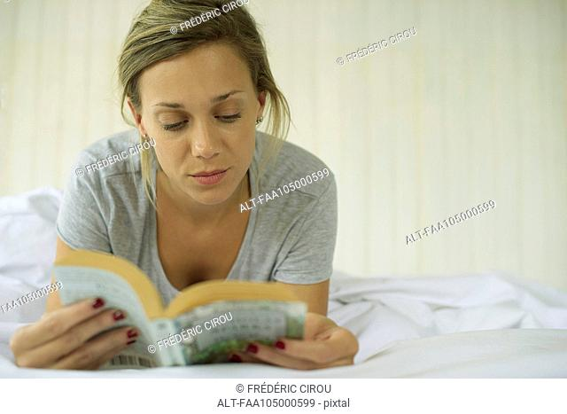 Woman lying on stomach reading book