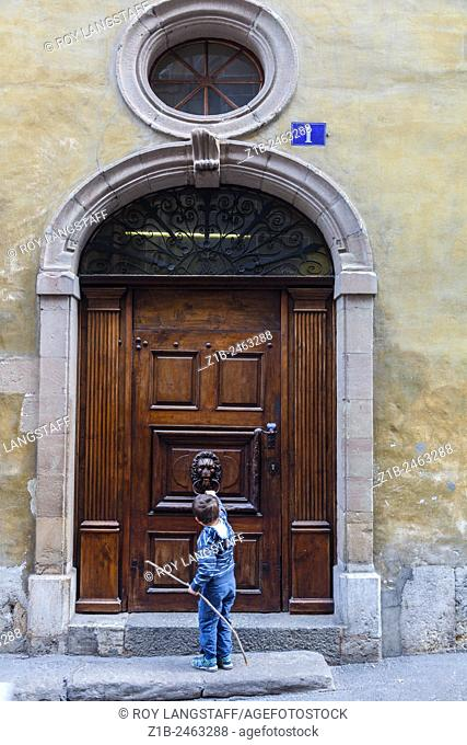 Young boy knocking on a large door in the old town of Geneva, Switzerland