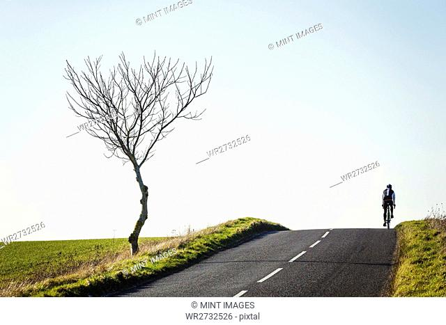 A cyclist riding along a country road on a clear sunny winter day, on the brow of a hill