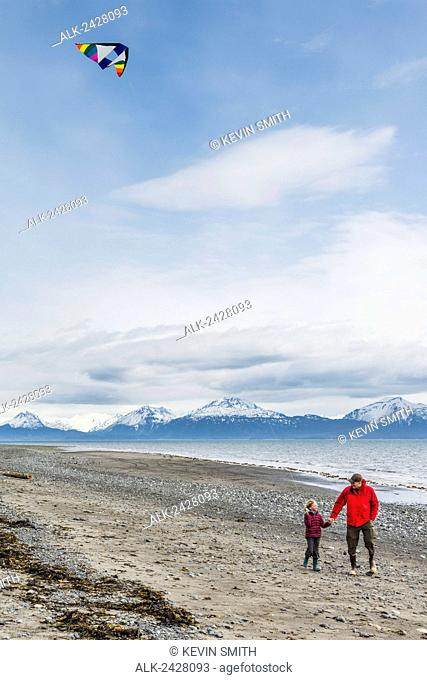 Father and daughter fly a kite on Bishop's Beach, Kachemak Bay, Homer, Southcentral Alaska, USA