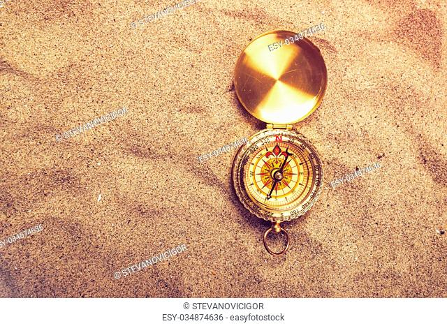 Top view of vintage compass on sandy beach, navigational equipment in warm brown sand of summer holiday vacation resort pointing to south