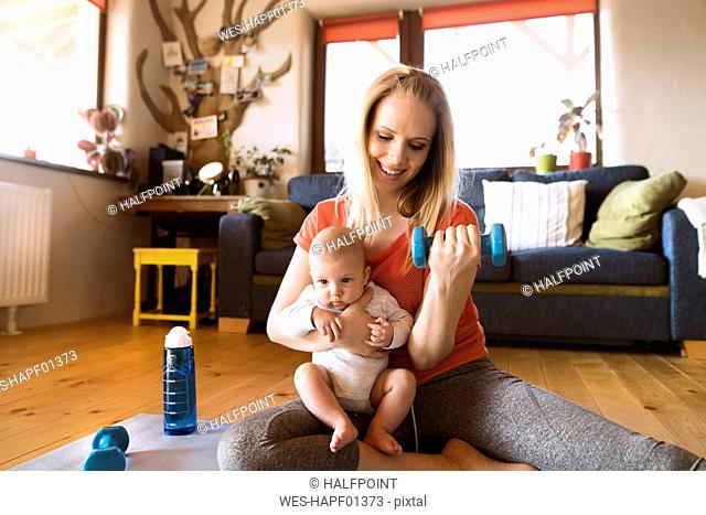 Smiling mother with baby exercising with dumbbell at home
