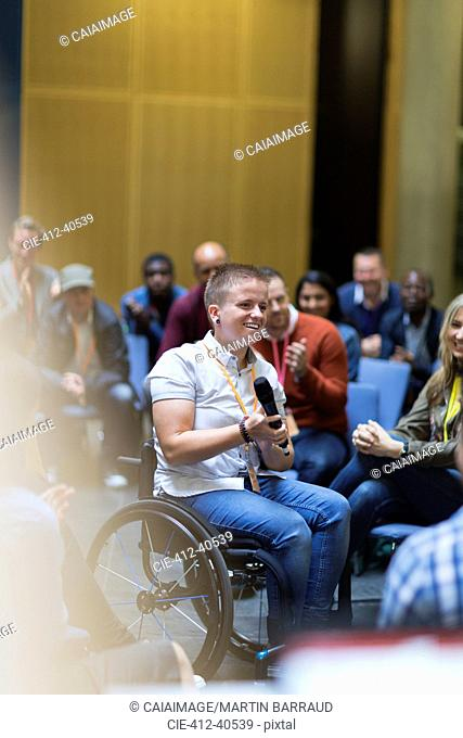 Smiling woman in wheelchair speaking with microphone in audience