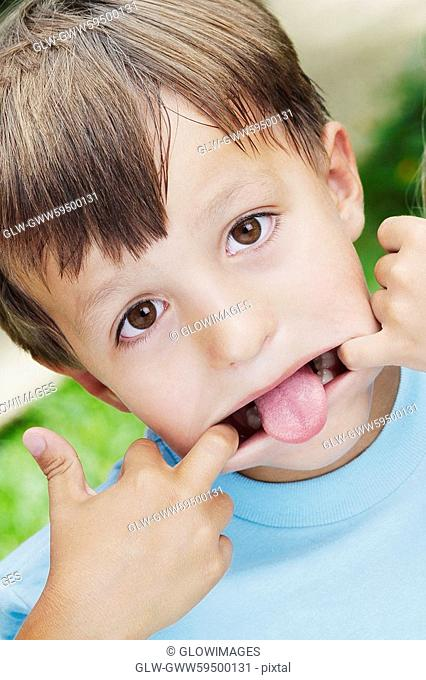 Close-up of a boy stretching his mouth with his fingers