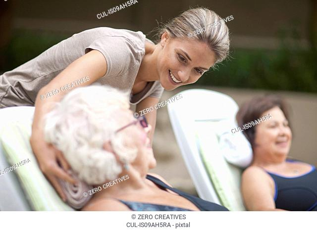 Senior women relaxing on loungers in retirement villa garden