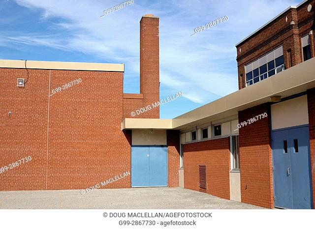 Playground area, smokestack and doors of an inner city Catholic elementary public school after school is out in Windsor, Ontario