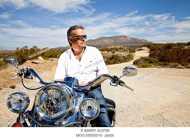 Senior man wearing sunglasses on motorcycle in desert