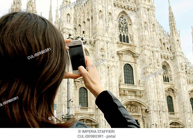 Over the shoulder view of female tourist photographing Milan Cathedral on smartphone, Milan, Italy