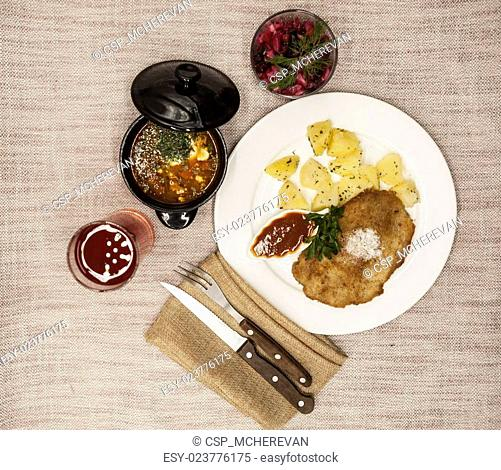 Business lunch : Petite Wiener schnitzel with boiled potatoes and ketchup. Served on a white porcelain plate with fork and knife on a wooden background