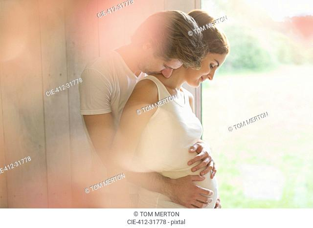 Affectionate pregnant couple hugging at window