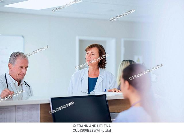 Senior male doctor thinking at nurses station in hospital