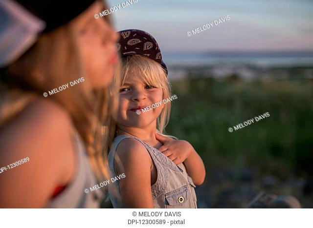 Sisters together on the beach at sunset; Surrey, British Columbia, Canada