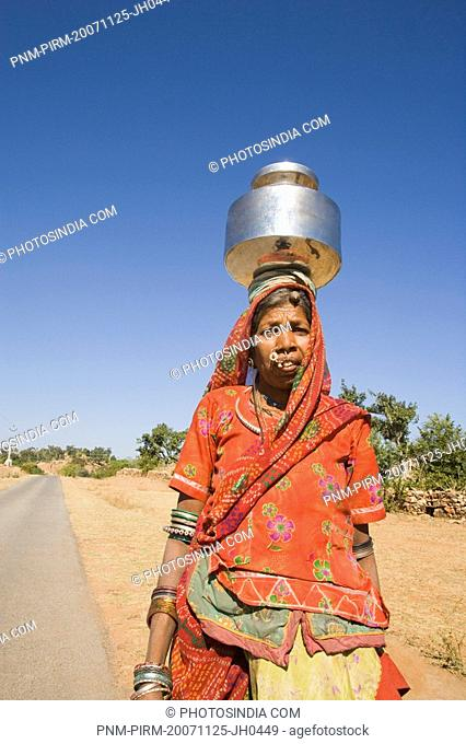 Woman carrying brass pot on her head, Kumbhalgarh, Udaipur, Rajasthan, India