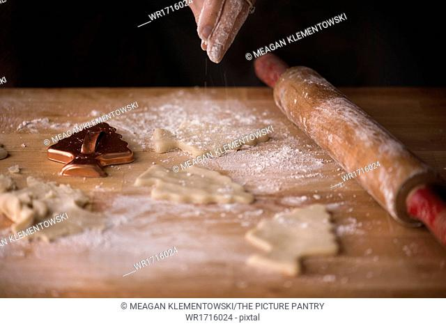 Woman sprinkling flour over sugar cookie dough cut into Christmas tree shapes. Antique rolling pin and cookie cutter on a butcher block surface