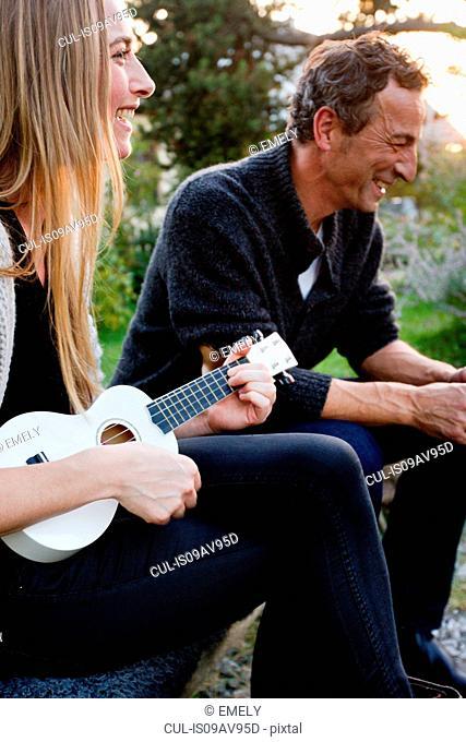 Couple sitting together, woman playing ukulele