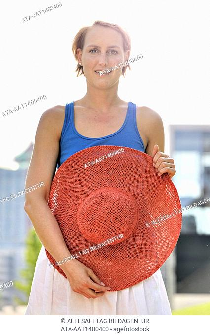 Woman with red straw hat in the sun