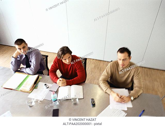 Businessmen sitting at table in office space