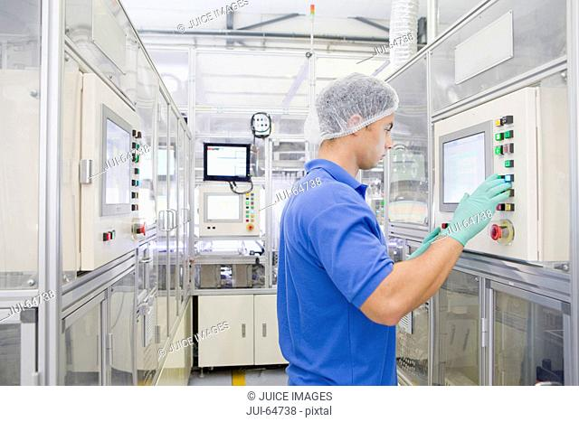 Technician worker controlling automated production line on factory floor