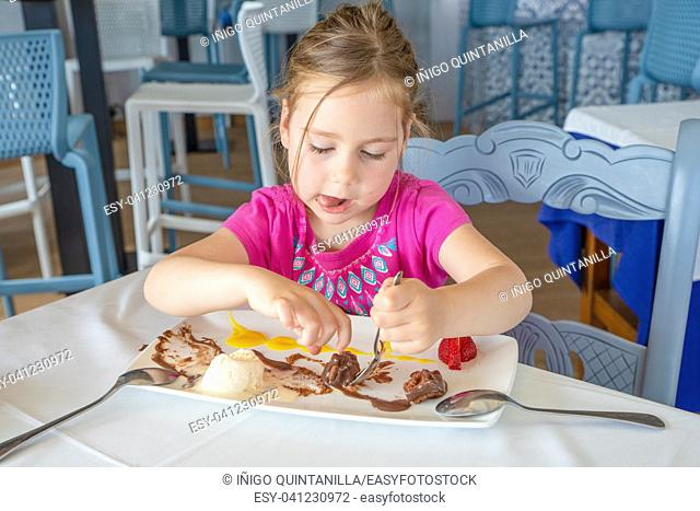 funny cute four years old blonde girl eating, and sticking out tongue, with spoon sweet dessert: black chocolate, vanilla ice cream