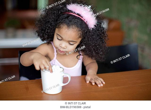 Mixed race girl drinking hot chocolate