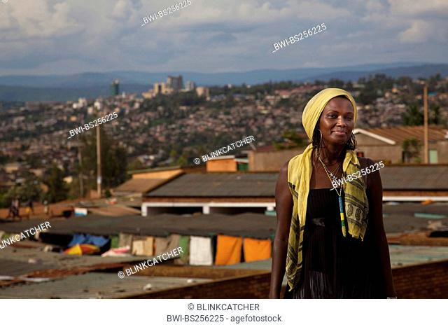 pretty young woman standing smiling in front city panorama with poorer and richer quarters contrasting, Rwanda, Nyamirambo, Kigali
