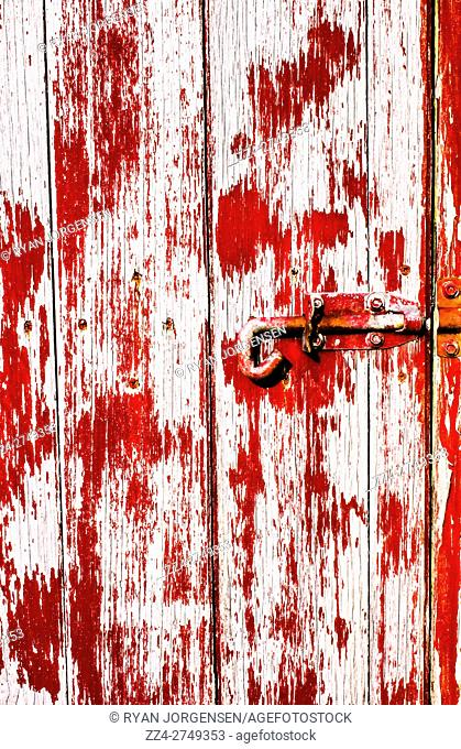 Grungy weathered old farm house door with peeling red paint and unlocked latch. Spooky enterances