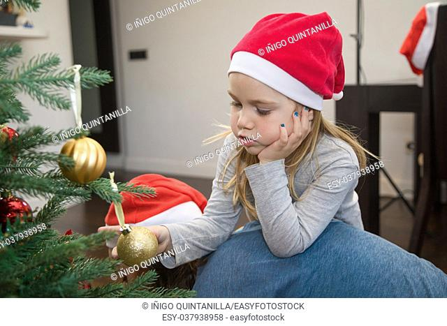 funny scene: four years blonde cute girl with red Santa Claus hat, holding a golden ball in Christmas tree, resting on her mother back, at home