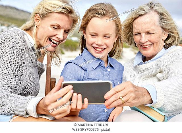 Mother, daughter and grandmother taking smartphone selfies on the beach