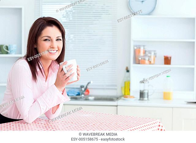 Happy woman with coffee cup in the kitchen