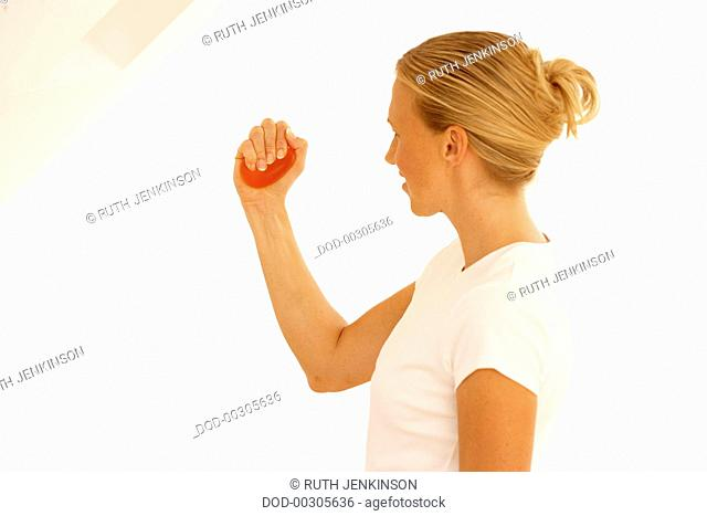 Woman wearing white t-shirt squeezing red ball