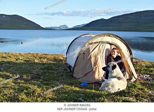 Tourist with dog in tent on lakeshore
