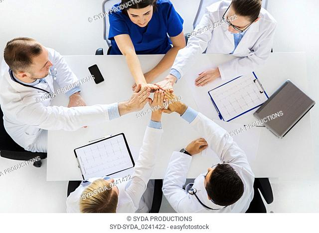 group of doctors making high five at table
