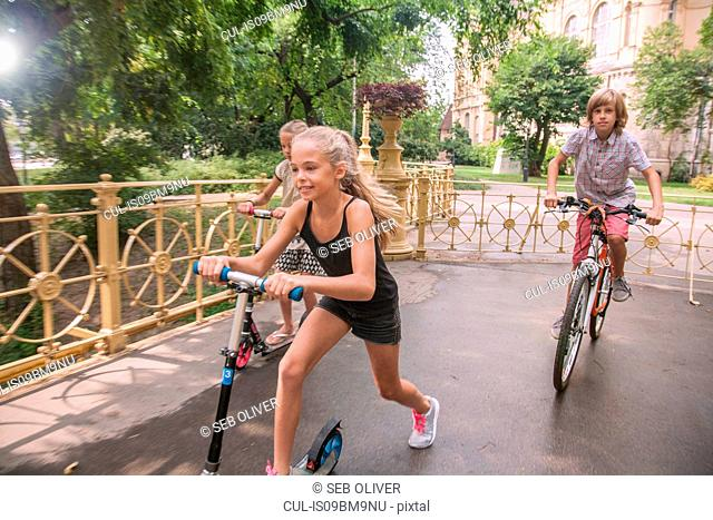 Children cycling and riding on scooter in park