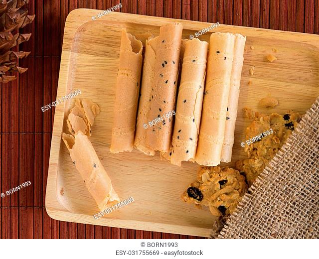 Thai rolled wafer and cookie in wooden tray on bamboo placemat