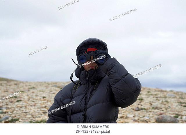 Teenager looking through binoculars on Mount Pelly, Ovayok Territorial Park, near Cambridge Bay; Nunavut, Canada