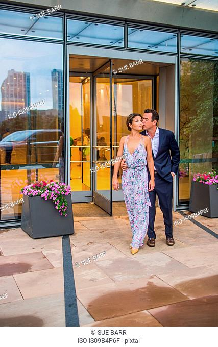 Couple standing together outside building, wearing evening clothes